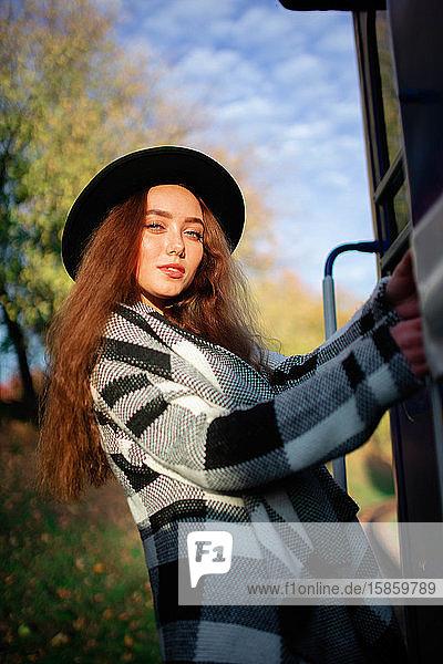 Porträt einer jungen Frau  die einen Eisenbahnwagen hält