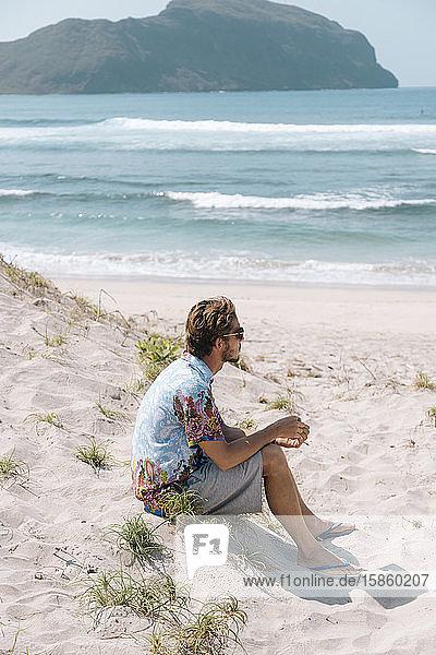 Junger Mann sitzt am Strand