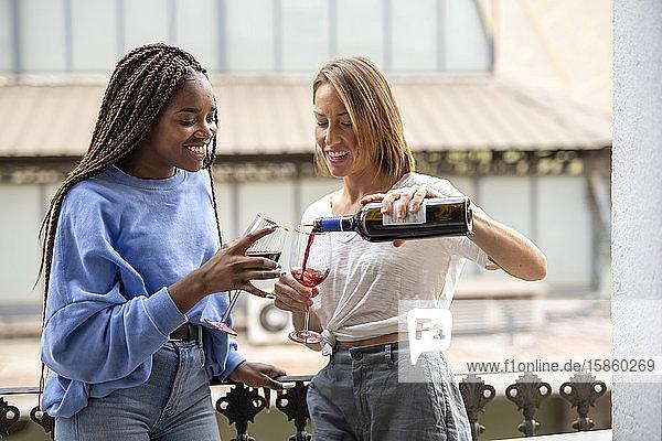 Ein befreundetes Paar trinkt Wein auf dem Balkon