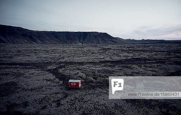 Kleines rotes Haus in dunklem  trockenem Gelände  umgeben von Hügeln