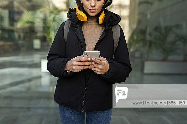 junge Frau  die mit gelben Kopfhörern Musik hört