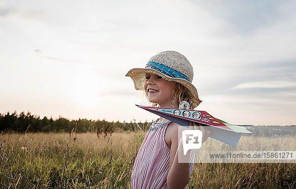 Porträt eines Mädchens  das bei Sonnenuntergang auf einer Wiese mit einem Papierflugzeug spielt