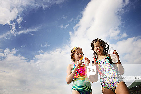 Two Young Girls in Swimsuits With Frozen Treats Against Blue Sky