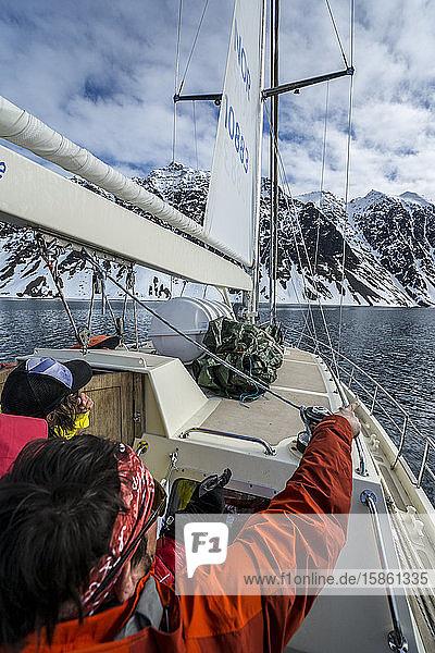 Friends on ski trip on sailboat going towards Jan Mayen