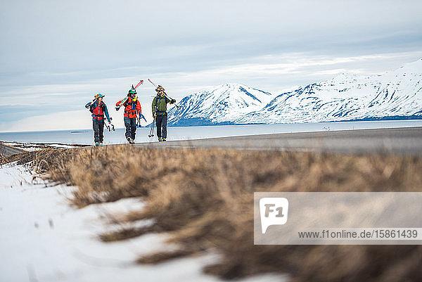 Drei Personen gehen auf einer gepflasterten Straße mit Bergen und dem Meer dahinter