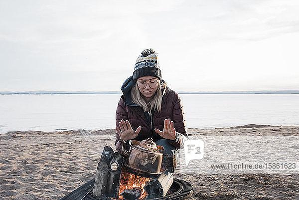 Frau,  die ihre Hände am Lagerfeuer wärmt und darauf wartet,  dass das Wasser kocht