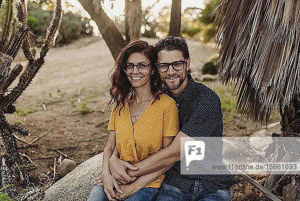 Mittelgroßes  erwachsenes Ehepaar sitzt auf einem Felsen und lächelt  während sie sich umarmen