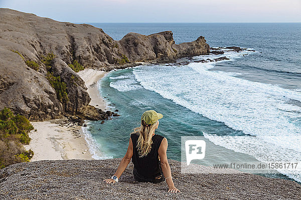 Junge Frau sitzt bei Sonnenuntergang auf einem Felsen