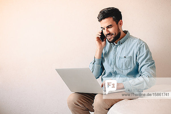 Happy businessman talking on smart phone while using laptop at home