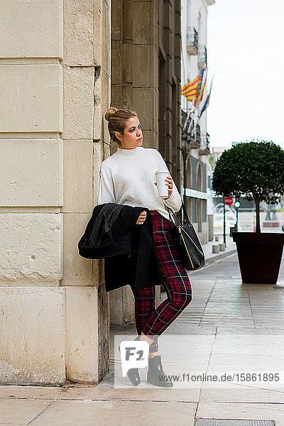 Junge Frau trinkt Kaffee und sieht sich auf der Straße um