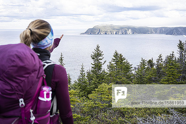 Female Backpacker Points At Cove On East Coast Trail In Newfoundland