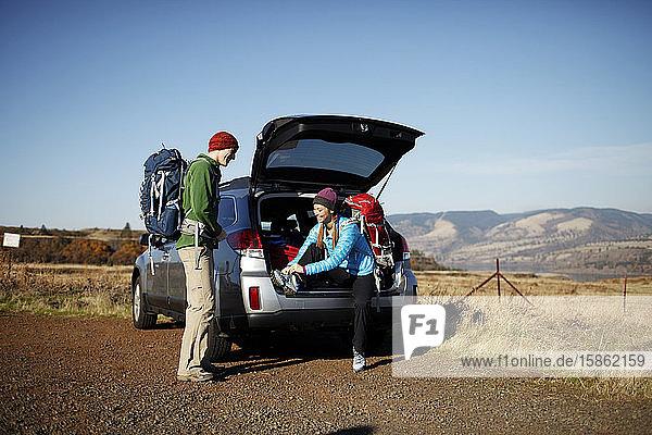 Mann und Frau machen sich mit dem Auto am Ausgangspunkt für die Wanderung bereit
