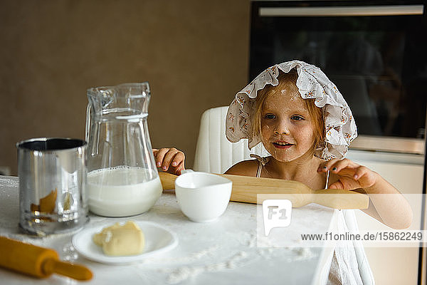 Little girl cooking pizza in the kitchen