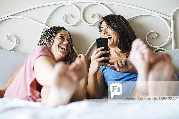 Zwei Frauen  die lachen  während sie auf einem auf einem Bett liegenden Handy Musik hören.