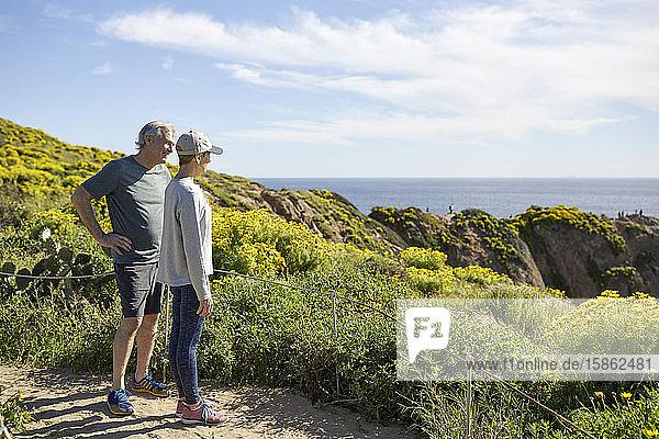 Älteres Ehepaar in voller Länge schaut auf das Meer  während es am sonnigen Tag auf einem Berg gegen den Himmel steht