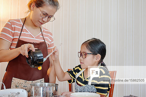 Mother and daughter add the yolk to mixing bowl