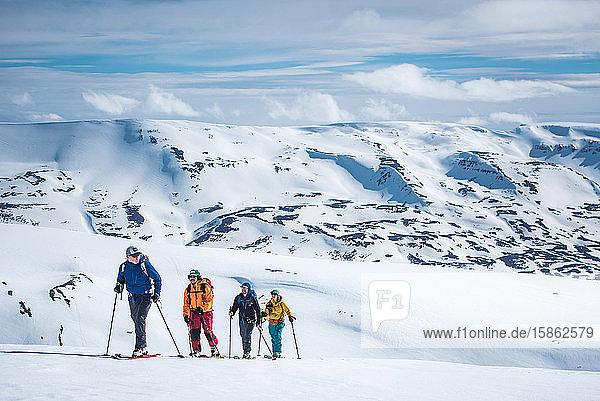 Eine Gruppe von Skifahrern auf Tournee in verschneiten Bergen in Island