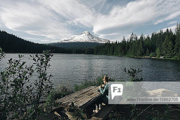Eine junge Frau isst am Picknicktisch an einem See in der Nähe des Mt. Hood zu Mittag.