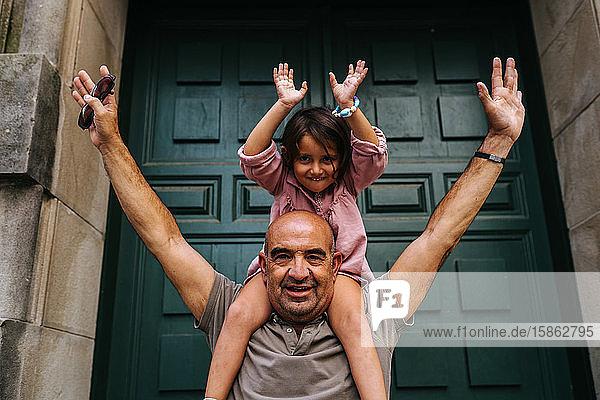 Großvater mit seiner Enkelin auf den Schultern  spielend  neben
