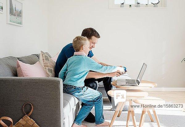 Vater und Sohn schauen zu Hause gemeinsam auf eine Kamera und einen Laptop