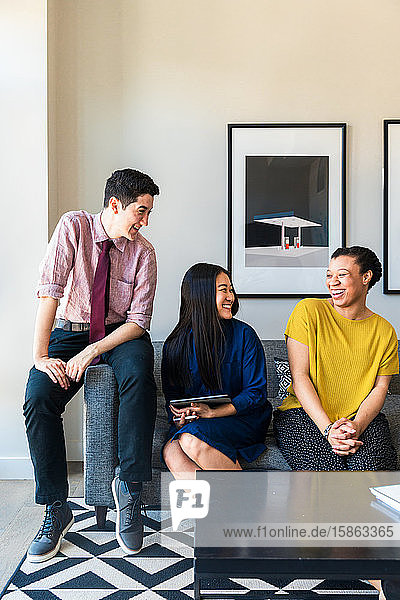 Lächelnde männliche und weibliche Geschäftskollegen unterhalten sich  während sie im Büro auf dem Sofa an der Wand sitzen