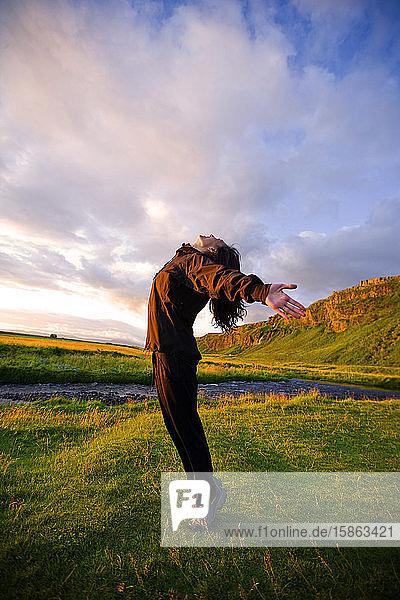 Chinesische Frau streckt sich bei Sonnenuntergang in Island