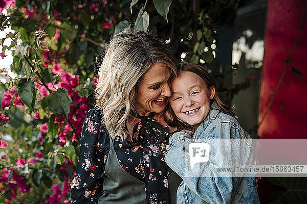 Lächelnde Mutter und Tochter vor roten Blumen an einem sonnigen Tag