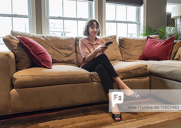 Junge Frau sitzt in Geschäftskleidung auf einer Couch und sieht fern.
