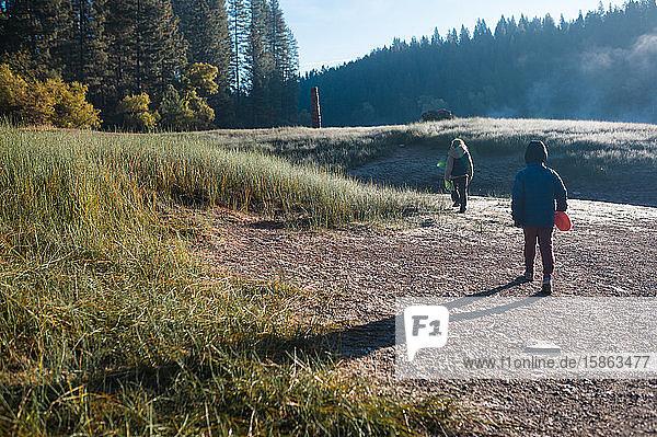 Zwei Kinder wandern an einem kalten Morgen auf einer Wiese