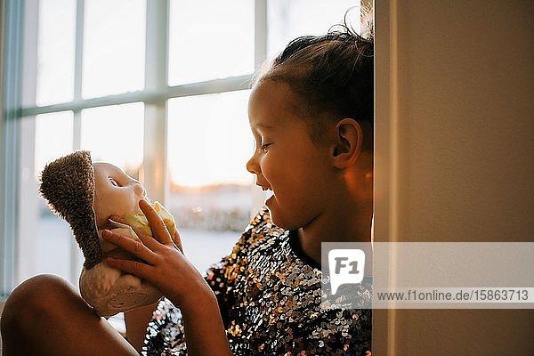 junges Mädchen lacht mit ihrem Spielzeug und spielt zu Hause in Schweden bei Sonnenuntergang