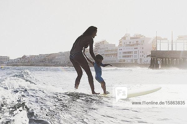 Gesamtansicht von Mutter und Sohn beim Surfen auf einer kleinen Welle auf See