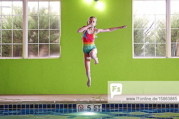 Junge Mädchen springen in einer Schwimmhalle