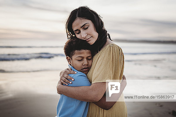 Portrait of mother embracing son during sunset with eeditorial closed