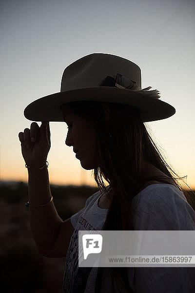 Eine Frau mit ihrem geliebten Cowboyhut erkundet den Sonnenuntergang in Joshua Tree