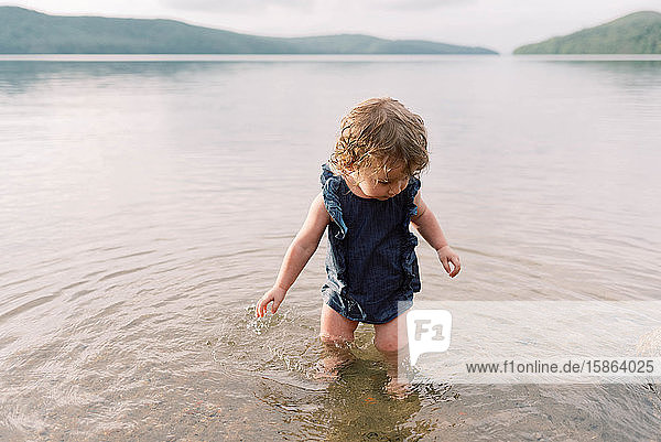 Little girl playing at a lake.