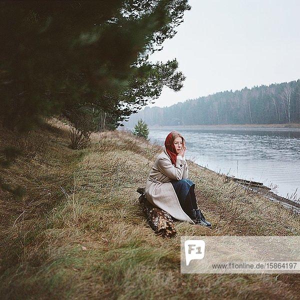 Frau mit rotem Schal am Fluss sitzend
