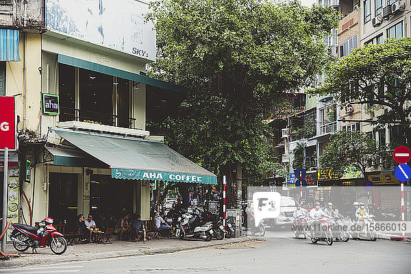 Street corner with motorbikes and a coffee shop with residential buildings; Hanoi  Vietnam