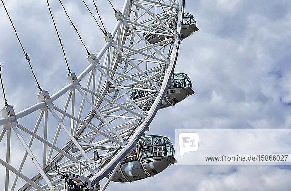Tourists in pods of the London Eye with a cloudy sky in the background; London  England