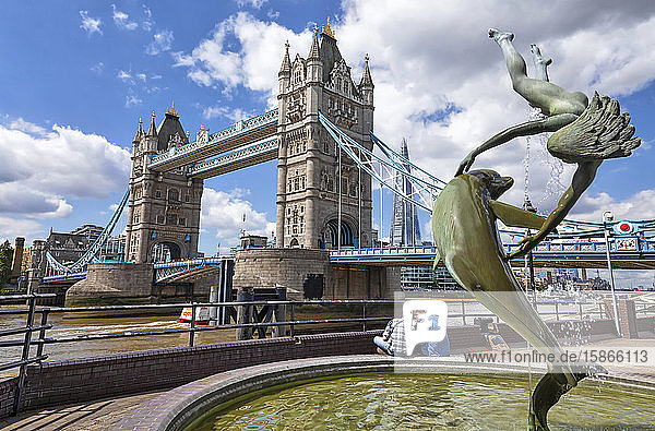 Tower Bridge on the River Thames and The Shard in the background with a fountain and tourists in the foreground; London  England