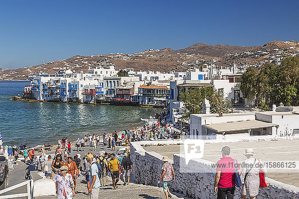Tourists on boardwalk leading down to waterfront houses in Little Venice area of Mykonos Town; Mykonos Town  Mykonos Island  Greece