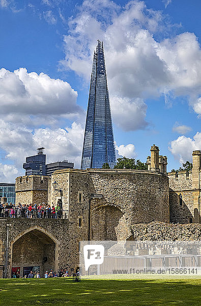 Tourists at the Tower of London with the Shard commerical skyscraper in the background; London  England