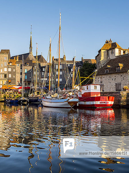 Boats reflected in the tranquil water of the harbour; Honfleur  Normandy  France