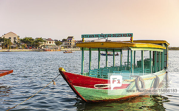 Colourful tour boat moored in the water along the waterfront at sunrise; Hoi An  Quang Nam Province  Vietnam