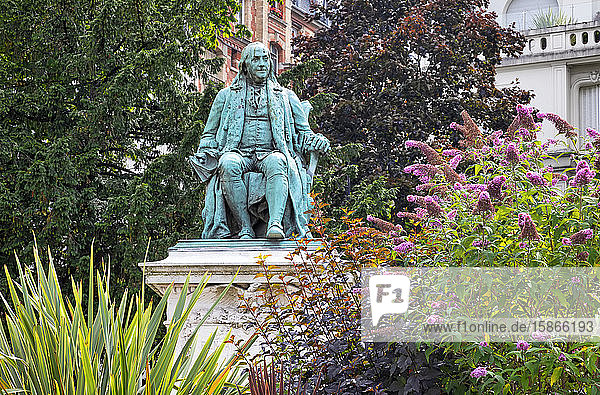 Benjamin Franklin statue in a garden with trees and blossoming plants; Paris  France