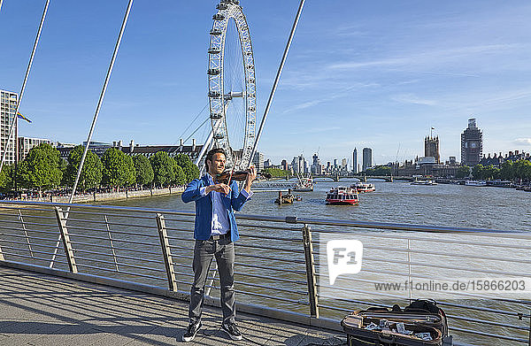 Busker playing violin on a bridge over the River Thames with boats and the London Eye in the background; London  England