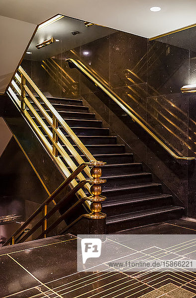 Staircase with brass handrails inside a building with dark brown flooring and walls; New York City  New York  United States of America
