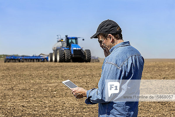 Farmer using a smart phone and tablet while standing on a farm field and watching the tractor and equipment seeding the field; Alberta  Canada