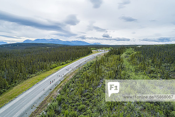 The mountains near Haines Junction during summer in the Yukon. Bikers ride along the Haines Highway during the annual Haines to Haines bike relay; Haines Junction  Yukon  Canada