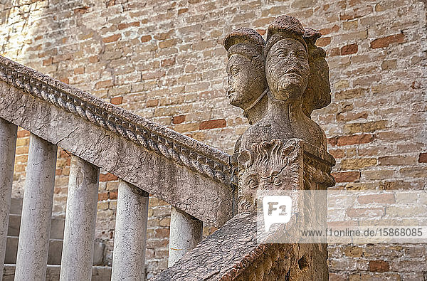 Carved stone sculpture of human heads and an animal face as a decorative post on a handrail beside a brick wall and stairway; Venice  Italy