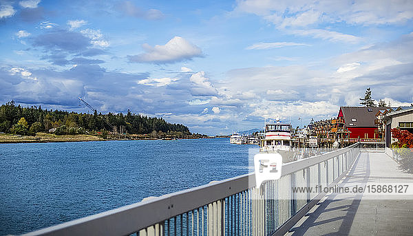Boats in the harbour and walkway to colourful buildings on the waterfront of La Conner  a town on the coast of the Pacific Northwest; La Conner  Washington  United States of America
